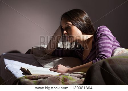 Young woman relaxing in her bed before sleep. She is reading a book.