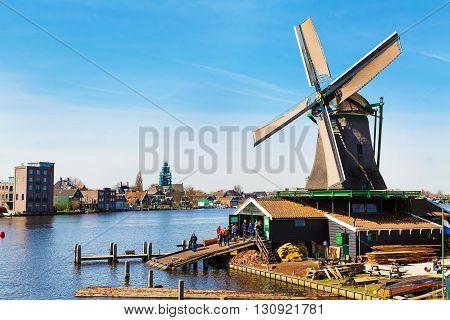 Zaanse schans, Netherlands - April 1, 2016: Windmill in Zaanse Schans, North Holland, traditional village, tourists, blue sky