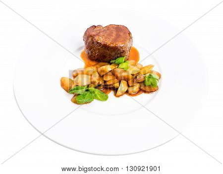 Delicious beef steak in demiglas sauce with vegetable garnish. Isolated on a white background.