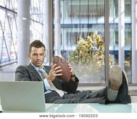 Relaxed businessman sitting at desk in front of office windows, holding football and smiling.