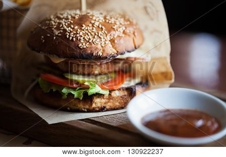 Delicious burger with lamb steak tomato cucumber and fresh salad fried on a grill and put between two bagels with sesame seeds. Unhealthy but so tasty junk food. Close up photo in macro mode no models
