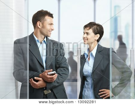 Two businesspeople standing in modern office with glass walls, looking at each other, smiling.