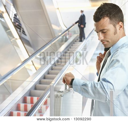 Businessman standing in office lobby looking at his watch, checking time.