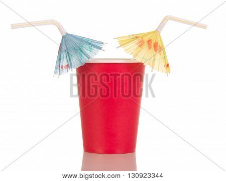 Red disposable cup with straw umbrellas isolated on white background.