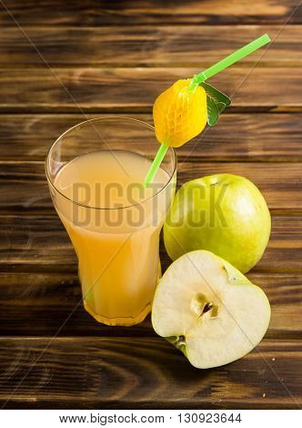 A glass of Apple juice and sliced Apple on a wooden Board