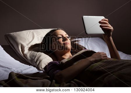 Young woman relaxing in her bed before sleep. She is using digital tablet.