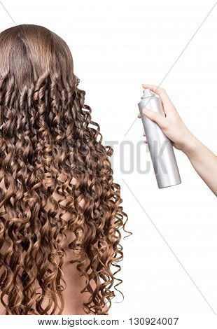 Woman with wavy hair and nail in the hand of the master isolated on white background.