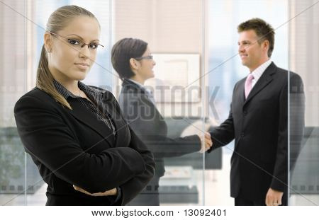 Confident young businesswoman standing in office, businesspeople shaking hands behind glass wall in background.