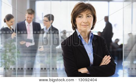 Senior businesswoman standing in corporate office,  businesspeople talking in background behind glass wall.