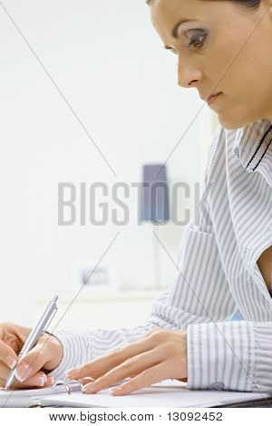 Young woman sitting at desk, writing notes into personal organizer.