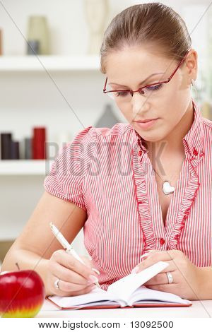 Attractive young woman sitting at table writing in diary book.