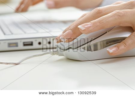 Closeup picture of computer keyboard and female hand clicks on mouse.