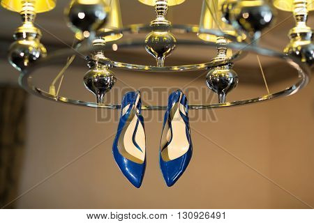 Female blue shoes on the silver chandelier