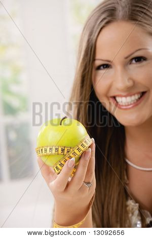 Happy young woman showing apple and tape measure, smiling.