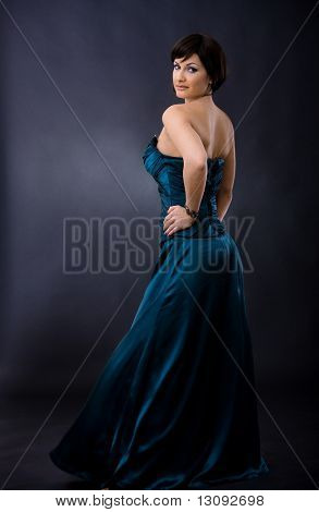 Studio portrait of beautiful young woman wearing dark blue evening dress, posing with hands on hip, smiling, looking back.