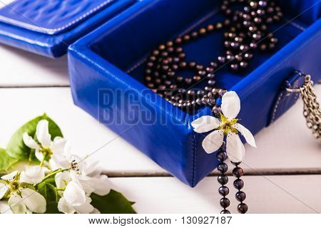 Leather jewelry box with a pearl necklace and branches of apple blossom