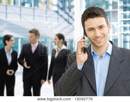 Retrato de hombre de negocios feliz hablando por móvil en el salón de la oficina.