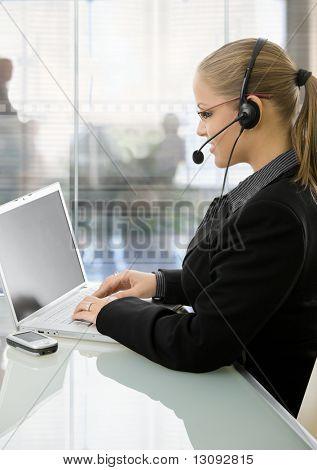 Joven empresaria sentado en el escritorio en la oficina moderna con paredes de cristal, usando la computadora portátil, hablando