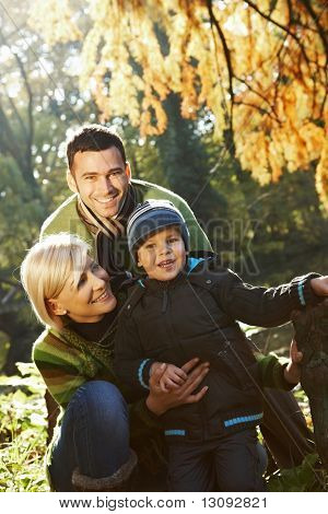 Happy family looking at camera, smiling outdoor in park at autumn.