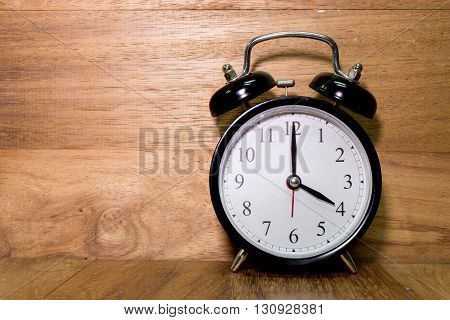 Vintage background with retro alarm clock on wood background Alarm clock shows Four o`clock