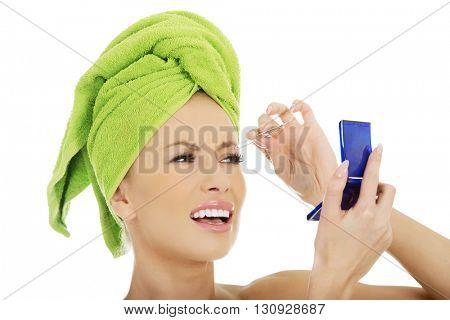 Beautiful woman plucking her eyebrow.