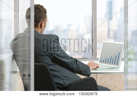 Businessman sitting at desk in office, working with laptop computer, looking out the windows.