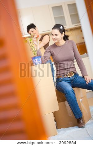 Young woman sitting on cardboard box looking at flower. Having a break during moving to new home.
