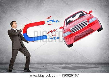 Businessman in suit holding big magnet attracting car