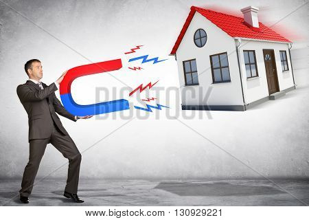 Businessman in suit holding big magnet attracting house