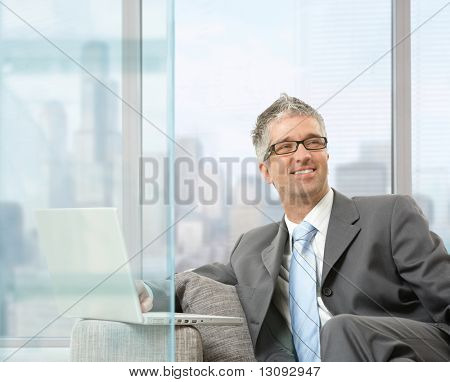 Happy businessman sitting on couch using laptop in modern glass office, smiling.
