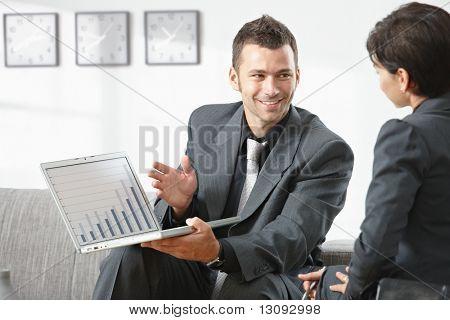 Joven empresario muestra gráfica financiera al socio en la oficina, sonriendo.