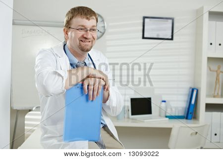Medical office - happy male doctor sitting on desk,holding file, looking away, smiling.