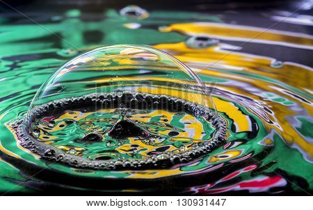 Water dropped through surface of soap bubble