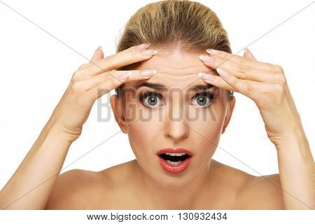 A young woman checking wrinkles on her forehead