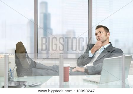 Relaxed businessman sitting at desk in corporate office, thinking.