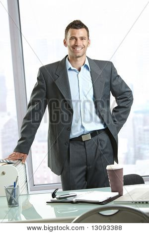 Happy businessman standing behind office desk, smiling.