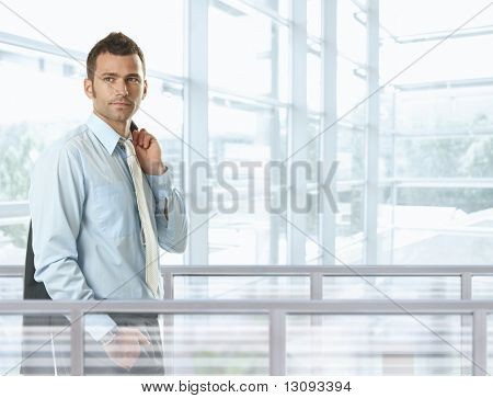 Casual businessman standing in front of glass walls in office lobby, smiling.