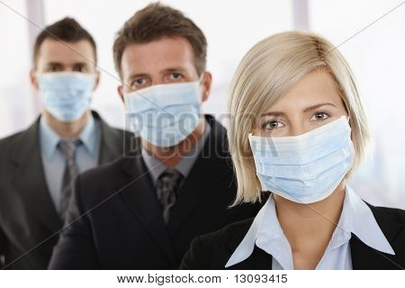 Business people fearing h1n1 swine flu virus wearing protective face mask and standing in a row.