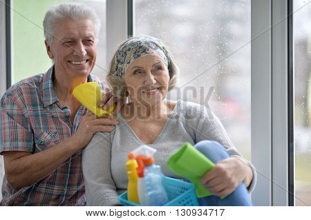 happy Senior couple cleaning window at home