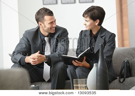 Happy young business people having meeting at office sitting on sofa working in team, smiling.