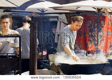 KYIV, UKRAINE - MAY 15, 2016: Sea-food cook preparing food in huge pan at outdoor party of Street Food Festival on May 15, 2016. Kiev is the 8th most populous city in Europe.