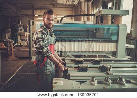 Carpenter doing his job in carpentry workshop.