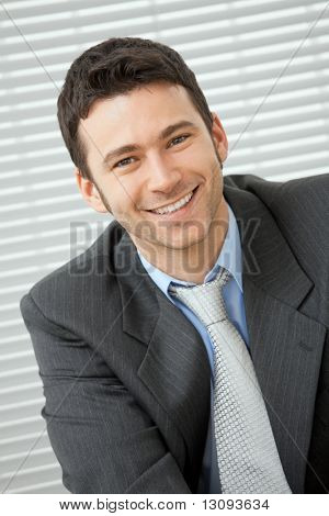 Portrait of happy businessman wearing grey suit and blue shirt, looking at camera, smiling.