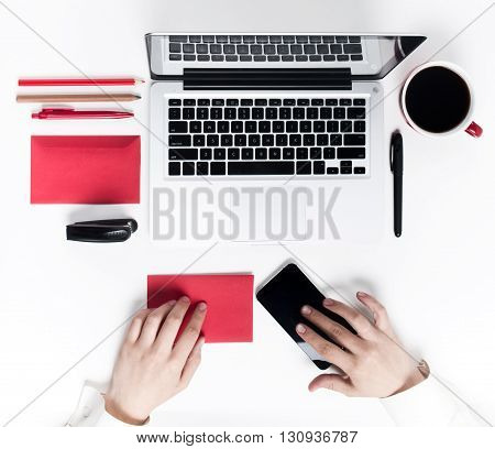 Concept of comfortable workplaces. Hands and gadgets on the white desk