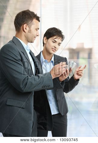 Two businesspeople standing in office lobby using smart mobile phone, smiling.