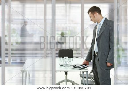 Businessman leaving modern glass walled meeting room, picking up his notes and organizer.