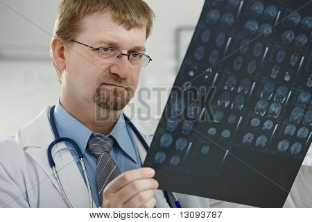 Medical office - portrait of middle-aged male doctor looking at computer tomograph scan.