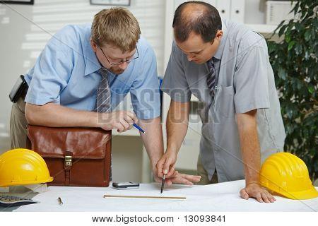 Arquitectos trabajando en la oficina - planificación y mirando el plano en el escritorio.
