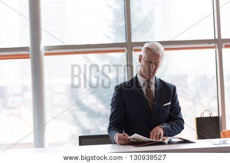 senior business man reading magazine at modern bright office