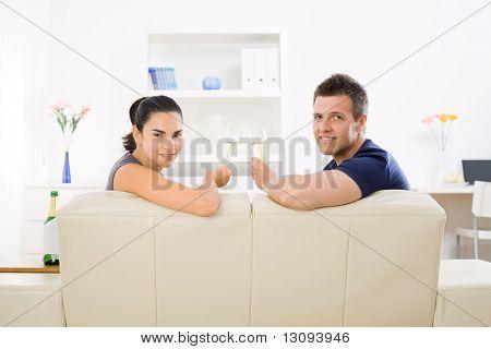 Amor pareja tintineo champagne gafas en casa en el sofá. Sonriendo y mirando a cámara.